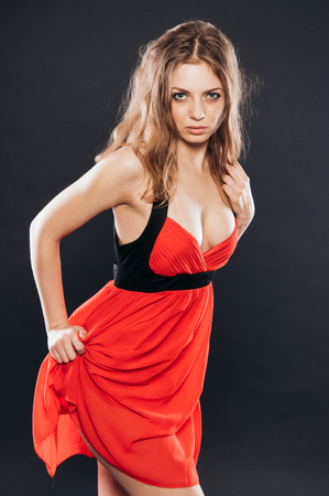 guile: Sexy young beauty woman with a beautiful look and long hair in red dress on gray background Stock Photo