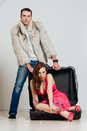 Cheerful couple going on a trip. Man in a fur coat