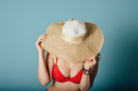 A summer girl with large breasts and a red bra covers her face with large hat on a blue background. Stock Photo