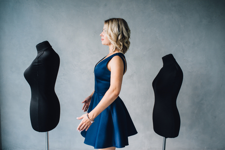 Woman fashion designer stands near the mannequins