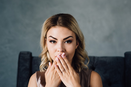 Surprised woman with hand over mouth