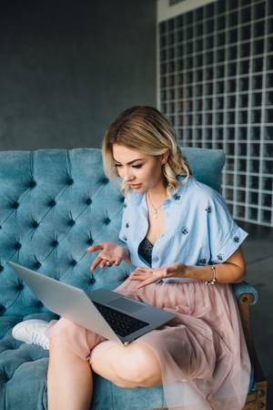 Happy woman sitting on couch using her laptop