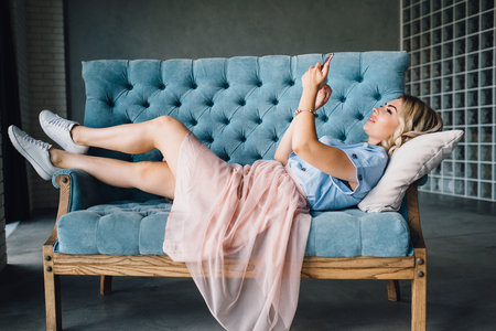 Beautiful woman is lying on the couch with phone