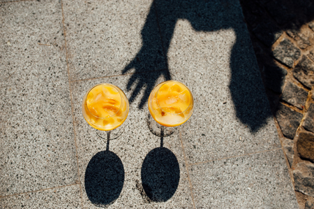 Two glasses with an orange cocktail with a shadow stand on the asphalt