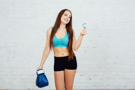 Girl boxer with braces holding gloves and cape Stock Photo