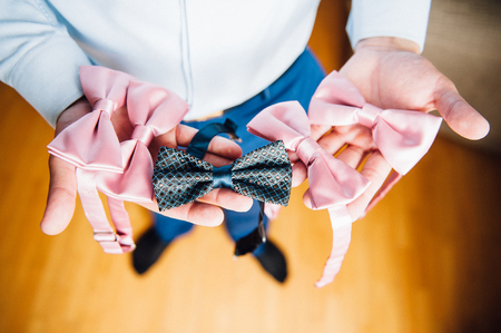 A man chooses a bow tie in his hands Stock Photo