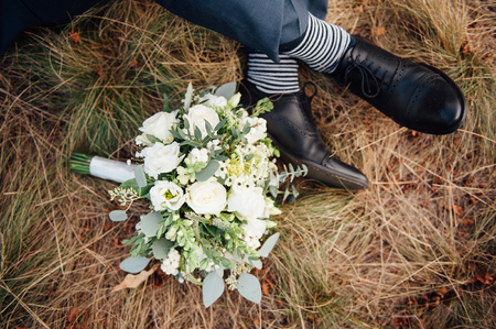 Close-up of wedding bouquet on brown grass with groom legs