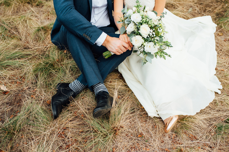 Wedding - Bride and groom are hugging and l sitting at a green grass Zdjęcie Seryjne