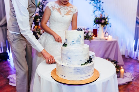 Beautiful delicious white wedding cake ceremony at the table
