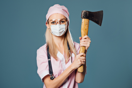 Serious lady doctor in respirator with ax