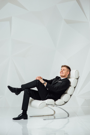 young business man in modern suit sitting on chair