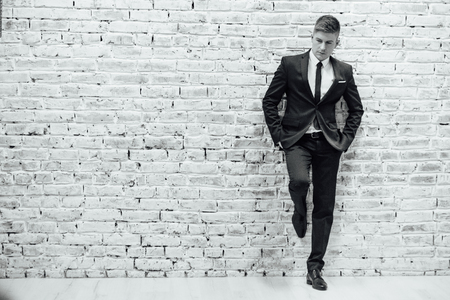 Young fashionable men in a suit against brick wall Stok Fotoğraf