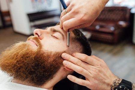 Close up image of barber makes beard cut of a man