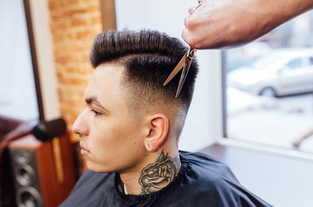 man getting trendy haircut at barber shop.