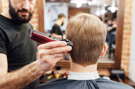 Close up shot of man getting trendy haircut at barber shop. The male hairstylist in tattoos serving client. Standard-Bild