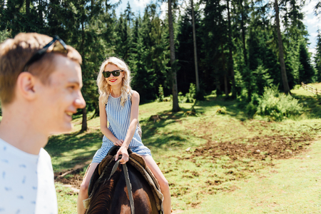 Beautiful couple riding on horses in the mountains
