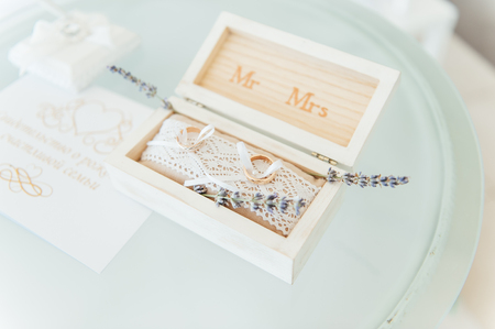 Side view shot of two gold wedding rings on flowers in old rustic wooden box for wedding ceremony. Фото со стока