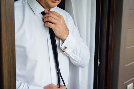 Close-up of a man in a tux fixing his vintage cufflink. groom bow tie cufflinks