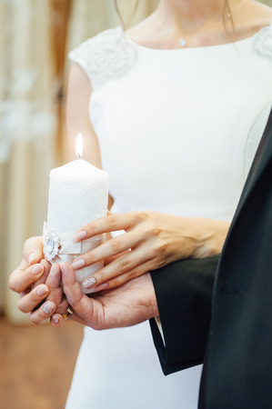Candle in the hands of the newlyweds symbolizes hearth and well-being of the family. Stock Photo