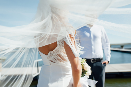Groom hugs bride tender while wind blows her veil