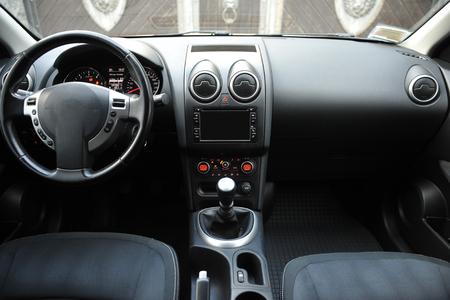 Modernes Luxus-Prestige-Autointerieur, Armaturenbrett, Lenkrad. Innenausstattung aus schwarzem perforiertem Leder. Kunststoffplatten. Isolierte Fenster