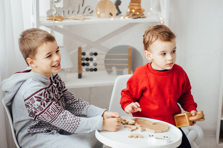 two brothers play puzzle on the table in the childrens room in the Scandinavian style