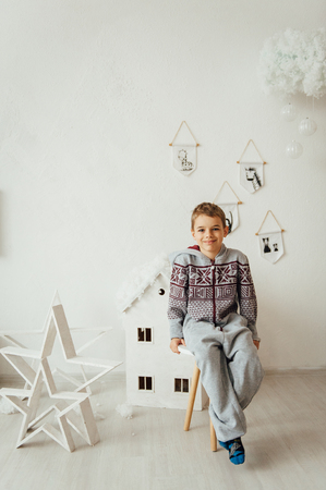 very cute and beautiful baby in pajamas sitting near a white wall. Standard-Bild - 116292772