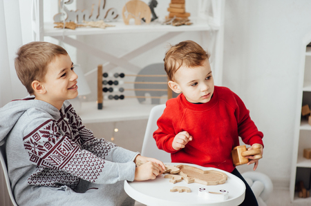 two brothers play puzzle on the table in the childrens room in the Scandinavian style Standard-Bild - 116292773