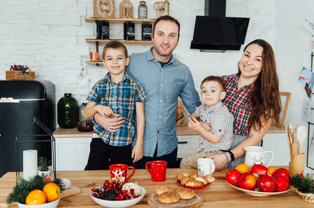 family of four embracing sitting on the kitchen. Two sons hug their parents Standard-Bild - 116292919
