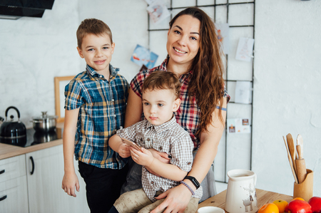 beautiful mother hugs her two sons on the kitchen Standard-Bild - 116292922