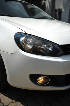 headlight of the main light of the white car, close-up. Standard-Bild - 116293645