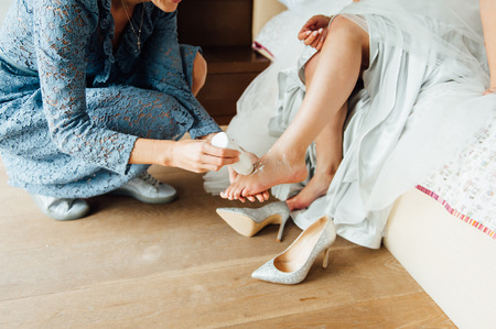 Wedding preparations. Bridesmaid applies powder to the brides leg to wear bridal shoes comfortably Standard-Bild - 116293982