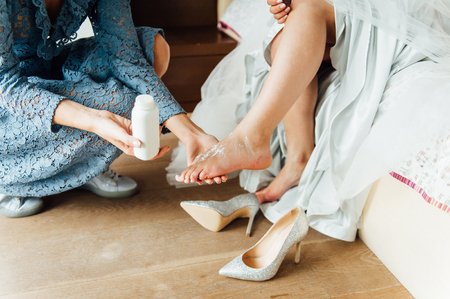 Wedding preparations. Bridesmaid applies powder to the brides leg to wear bridal shoes comfortably Standard-Bild - 116293986
