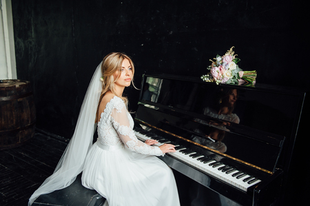 Incredibly beautiful bride plays the piano. Wedding day