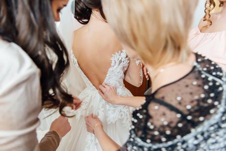 Bridesmaid preparing bride for the wedding day. Wedding concept Stock Photo