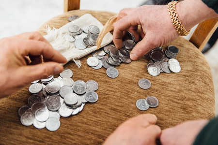 Beggar old man considers coins to buy food