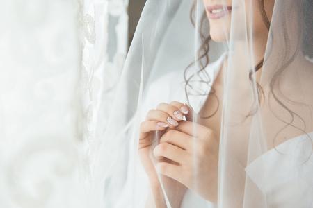 Braut in einem Hochzeitskleid und Schleier, die auf das Fenster schaut und am Morgen auf den Bräutigam wartet Standard-Bild