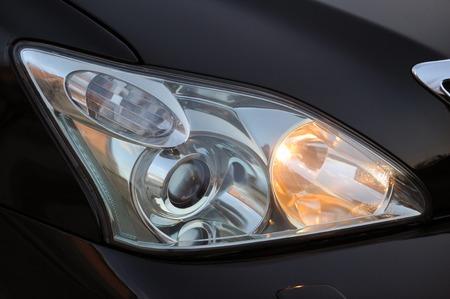 Scheinwerfer des Hauptlichts des schwarzen Autos, Nahaufnahme.