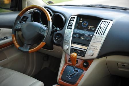 Modern luxury prestige car interior, dashboard, steering wheel. Perforated leather, wooden interior.