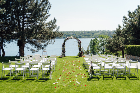 beautiful arch for the wedding ceremony in the park with white chairs for guests Stock Photo