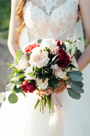 Beautiful bride is holding a wedding colorful bouquet.
