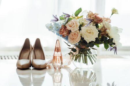 Hochzeitsset der Braut. Beige Schuhe, Parfüm und ein schöner Strauß liegen auf dem Marmorboden
