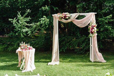 arco di nozze e sedie sull'erba verde nel parco. Decorazione di cerimonia di nozze.