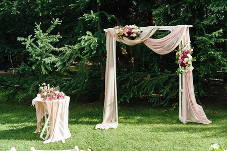 wedding arch and chairs on the green grass in the park.Wedding ceremony decoration.