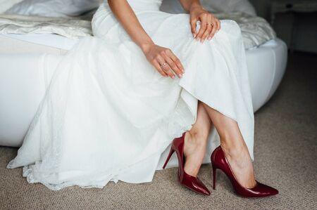 bella sposa in un vestito indossa scarpe rosse al mattino.