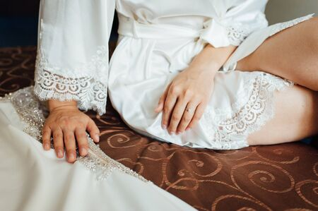 Hands of a young woman are laying on her legs, she is sitting on the chair. She is wearing white pyjamas.