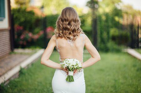 La novia se pone un calcetín de espaldas al marco y sostiene un ramo de flores de colores. frente a ella hay arboles y pasto verde
