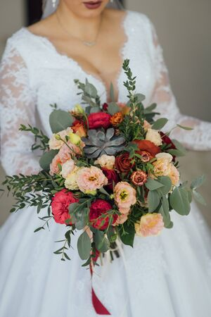 bride in a white dress holding a bouquet of flowers and greenery Banque d'images - 132058864