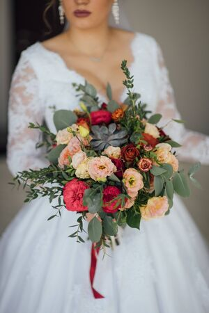 bride in a white dress holding a bouquet of flowers and greenery Banque d'images - 132057626