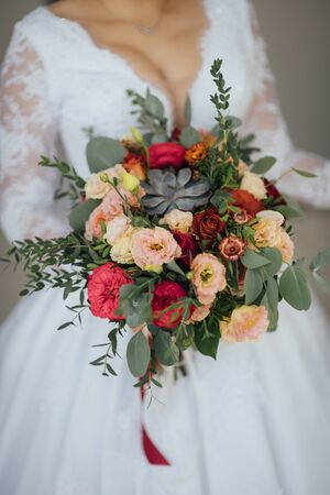 bride in a white dress holding a bouquet of flowers and greenery Banque d'images - 132058944